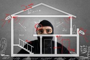 Einbrecher betrachtet Skizze vom Haus um die Alarmanlage zu umgehen