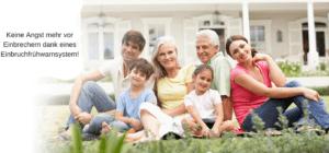 eine glückliche Familie auf der Wiese gesichert durch eine Alarmanlage