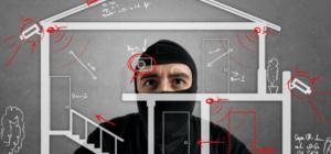 Einbrecher betrachtet die Skizze eines Hauses und die darin befindliche Alarmanlage